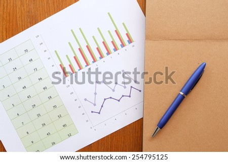 chart and note book on the wooden table