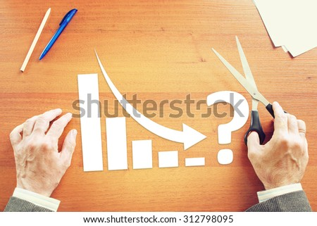 Chart of Business Decrease  With an Arrow Falling Down. Concept of Crisis With Paper Scrapbooking - stock photo