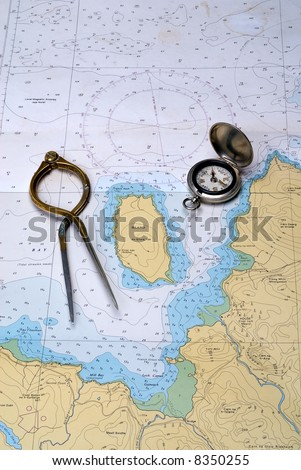 Charting the course. Antique navigation instruments on an old well used nautical chart - stock photo