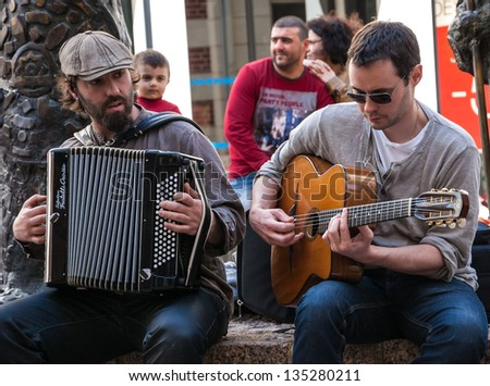 CHARTRES, FRANCE - APRIL 14: Two unidentified street musicians and the public as seen on April 14, 2013 in Chartres, France Hundreds of buskers perform on the streets in France. - stock photo