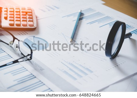 charts and graphs with magnifying glass and pencil, calculator, clock. Reflection light and flare. Concept image of data gathering and statistical working.