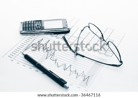Charts, pen, cell phone and glasses - stock photo