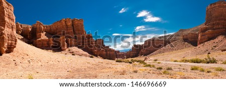 Charyn canyon under blue sky. State National Paleontology Park in Kazakhstan. Three images panorama