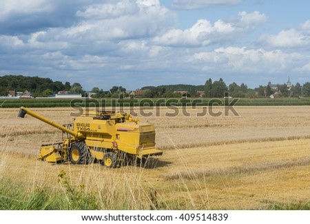 Chateauneuf-sur-Loire, France - August 2, 2012: Threshing machine on a field near a small village.