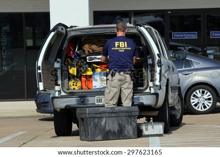 CHATTANOOGA, TN/USA - JULY 18: An FBI agent gathers evidence at the Armed Forces Career Center in Chattanooga, TN on July 18, 2015. An attack on the center was carried out on July 16th, 2015. - stock photo