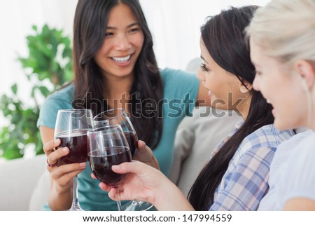 Chatting friends having red wine together at home on couch - stock photo
