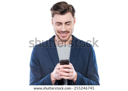 Chatting with friend. Handsome young man typing message on mobile phone and smiling while standing against white background - stock photo