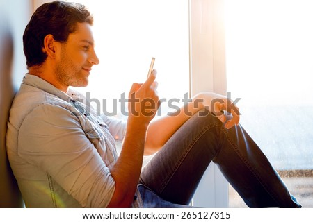Chatting with friend. Side view of handsome young man sitting at the window sill and holding mobile phone - stock photo
