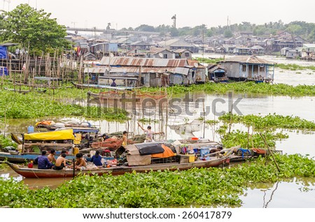CHAU DOC, VIETNAM - JANUARY 2, 2013: Rural life: Local fishermen' families living on their boats in port on Hau River (Bassac River) in Chau Doc in Mekong Delta - stock photo