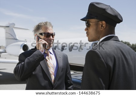 Chauffeur looking at senior businessman on call with private jet in the background - stock photo