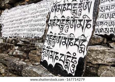 CHAURIKHARKA, NEPAL - CIRCA OCTOBER 2013: Mani stones with the inscription mantra is one of the elements of the Buddhist religion circa October 2013 in Chaurikharka. - stock photo