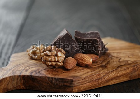 chcolate pieces with almonds and walnuts, on wooden board - stock photo