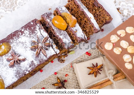 Chcolate spices cake with star anise and dried fruits, cinnamon, cloves, cardamom, handmade milk chocolate with nuts on sackcloth, canvas. Christmas gift. - stock photo