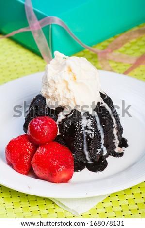 chcoolate lava cake with vanilla ice cream and fresh strawberries - stock photo