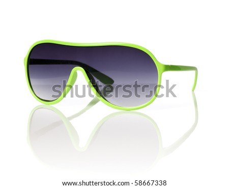 Cheap green plastic 1980s style sunglasses on reflective background. - stock photo