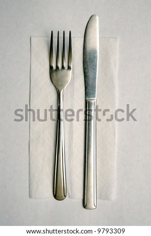 Cheap metal knive and fork on paper napkin, laid out for use