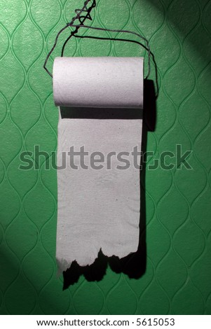 Cheap toilet paper roll on the green wall. You can write your message on it. - stock photo