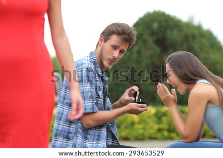 Cheater man cheating during a marriage proposal with his innocent girlfriend - stock photo