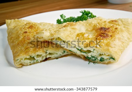 Cheburek  with cheese- traditional Caucasian dish.national dish of the Crimean Tatars and  Caucasian and Turkic peoples,  popular  Transcaucasia, Central Asia, Russia, Ukraine,  in Turkey and Romania. - stock photo