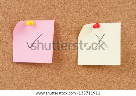 Check and cross mark drawn on paper and pinned on cork board - stock photo