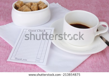 Check and cup of coffee on table close-up - stock photo