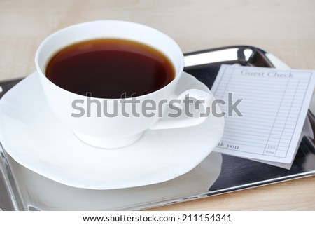 Check and cup of coffee on tray close-up - stock photo