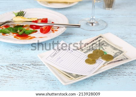 Check and remnants of food on table in restaurant  - stock photo