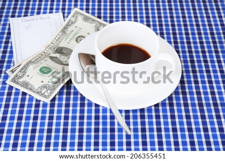 Check, cup of coffee and money on table close-up - stock photo