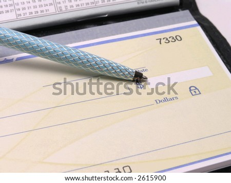 Check in checkbook with pen pointing at dollar amount - stock photo