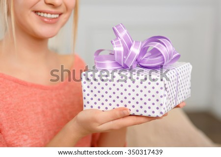 Check it out. Young pleasing woman is smiling while upholding wrapped gift box.
