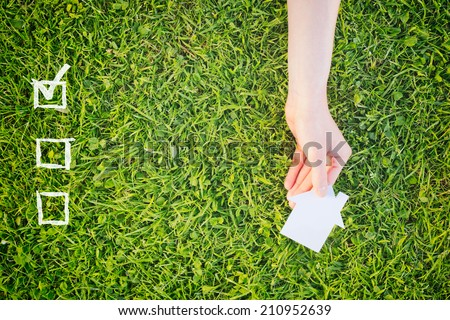 Check list for buying a new house or property with a hand holding a white house over green grass. - stock photo