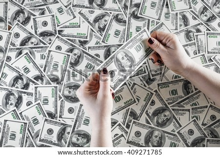 Check the authenticity of money. One hundred dollar bill in female hands on a background of money. Checking money. Cash in hands. Fake money in hands. Money in female hands. - stock photo