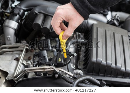 check the oil  in modern car motor  - stock photo