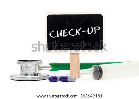 CHECK-UP concept with text on chalkboard with stethoscope, syringe and pills - stock photo