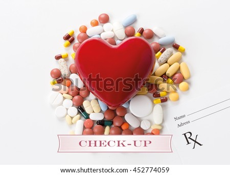 CHECK-UP written on heart and medication background - stock photo