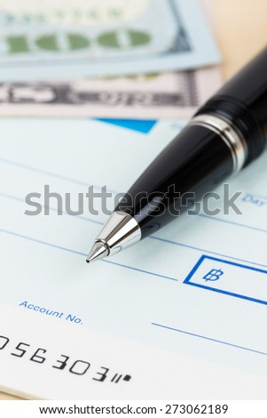 Check with pen and banknote