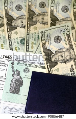 Checkbook on top of tax refund check and 1040 tax form on lots of paper cash ready to be deposited. - stock photo