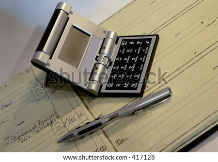Checkbook open, with a pen and multi-function international calculator laying on top. Shot from a high angle on a neutral background. Lighting from right casts shadows on left. Horizontal composition - stock photo