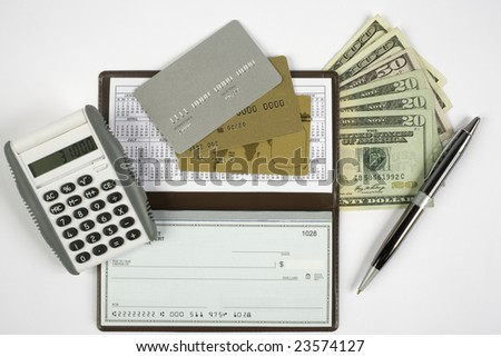 Checkbook open with blank check showing along with a calculator, pen, cash, and credit cards. - stock photo