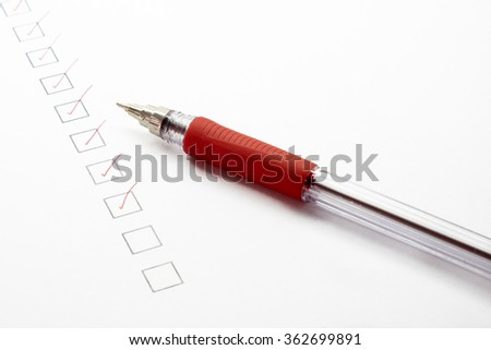 Checked list paper and red pen - stock photo