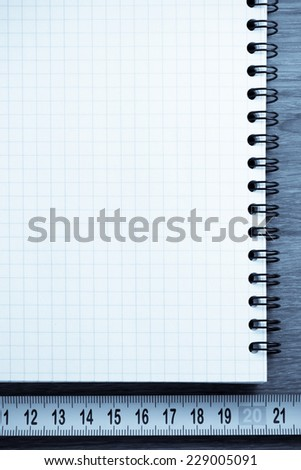 checked notebook on wooden background - stock photo
