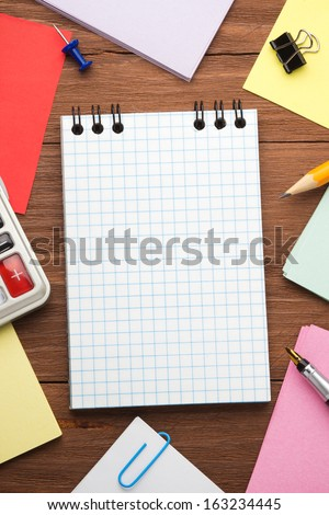 checked notepad and office accessories on wood background - stock photo