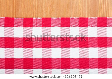 Checked with red and white tablecloth on a wooden table - stock photo