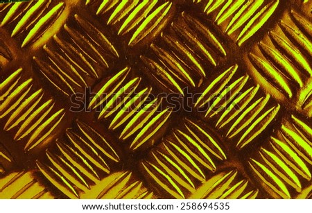 Checker plate style surface texture background on golden green colored filter represent the texture background related concept idea. - stock photo