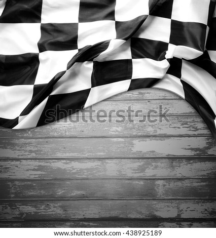 Checkered black and white flag on boards. Copy space - stock photo