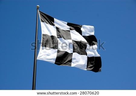 Checkered flag against a clear blue sky - stock photo
