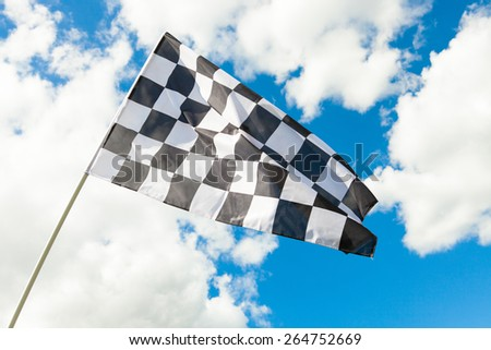Checkered flag with cumulus clouds behind it - stock photo