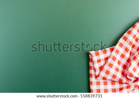 Checkered napkin on green board background