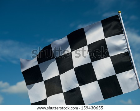 checkered race flag waving on blue sky.
