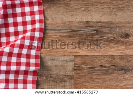 Checkered table cloth on a wood table with copy space, horizontal format.  - stock photo